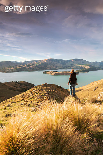 Hiker looking at view at sunrise, New Zealand - gettyimageskorea