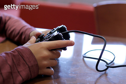 Close-up of boy hands playing video game - gettyimageskorea