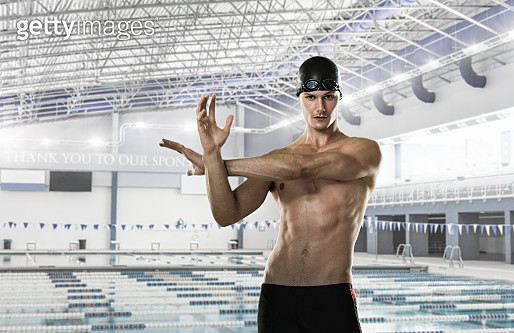 Male swimmer stretching by swimming pool - gettyimageskorea