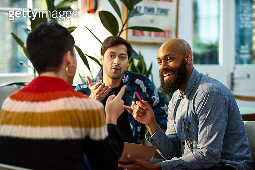 Multi ethnic group sharing ideas in office - gettyimageskorea