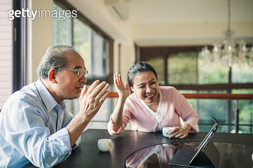 Man and woman, senior married couple digital tablet to talk with family, sitting at home together. - gettyimageskorea