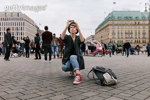 A Tourist Kneeling Down Taking Photo - gettyimageskorea