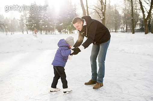 Father and daughter ice skating on frozen lake - gettyimageskorea