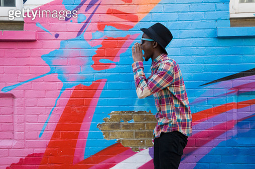Black man in sunglasses shouting near colorful wall - gettyimageskorea