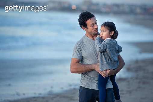 A middle age father holding his 3 year old while walking on a stretch of ocean beach in Los Angeles. - gettyimageskorea