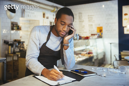 Confident young male employee talking through smart phone while writing on clipboard at delicatessen - gettyimageskorea