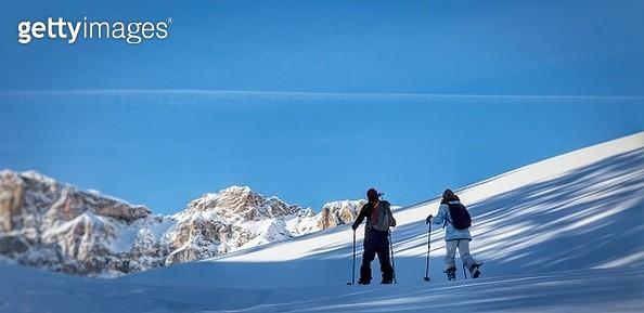 People Walking On Snowcapped Mountain Against Blue Sky - gettyimageskorea