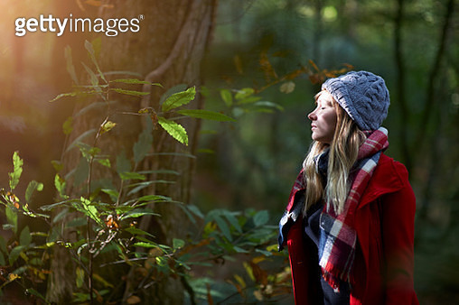 Woman in forest with sunlit face and closed eyes. - gettyimageskorea