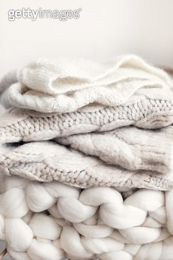 Stack of cozy wool white knitted sweaters on wicker armchair. Pile of merino and cashmere winter clothes. Hygge style. Warm concept. - gettyimageskorea