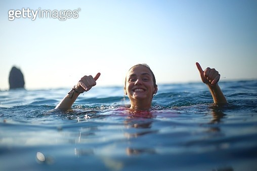 Portrait Of Smiling Young Woman Swimming In Sea - gettyimageskorea