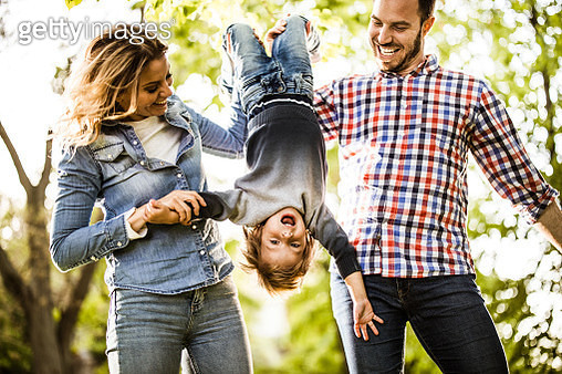 Young happy parents having fun while holding their small son upside down in nature. - gettyimageskorea