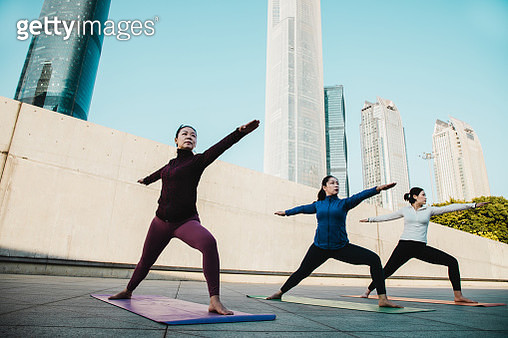 Senior Asian woman practicing yoga with two young woman - gettyimageskorea