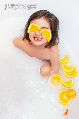 Baby girl takes milk baths with oranges. - gettyimageskorea