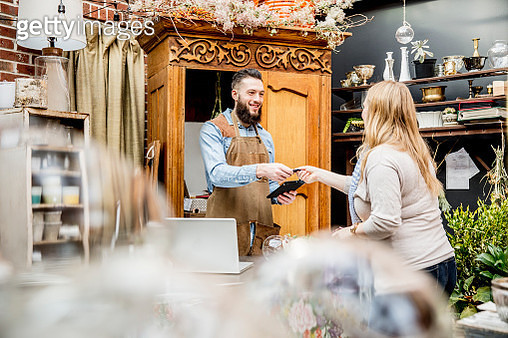 Employee helping customer shopping in store - gettyimageskorea