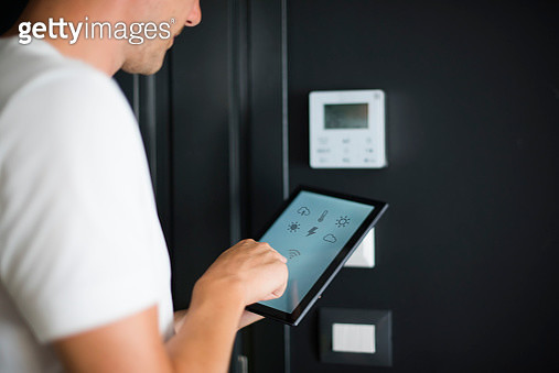 Man using digital tablet with smart home control functions - gettyimageskorea