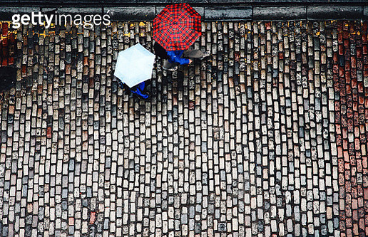High angle view of cobblestone street and umbrellas - gettyimageskorea