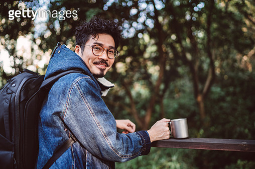 Young asian man with reusable coffee cup smiling joyfully at camera in country park - gettyimageskorea