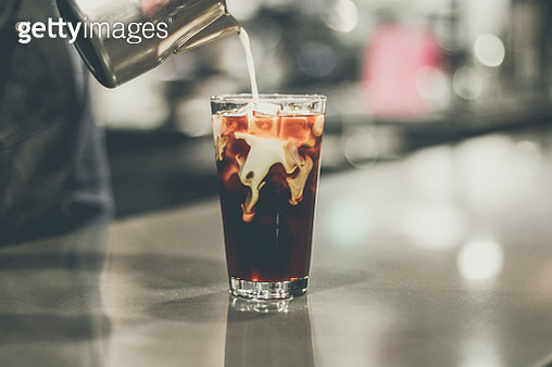 Close-Up Of Hand Pouring Milk In Coffee - gettyimageskorea