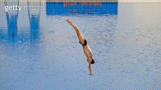 Side view of young man diving into swimming pool. - gettyimageskorea