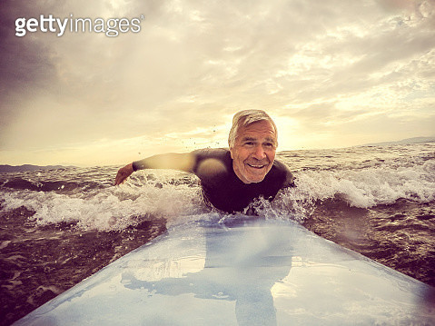 Very active senior man, surfing on a wave with a surfboard - gettyimageskorea