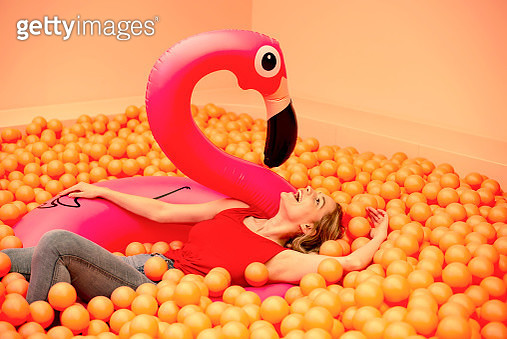 Cheerful young woman with inflatable flamingo lying in orange ball pit - gettyimageskorea