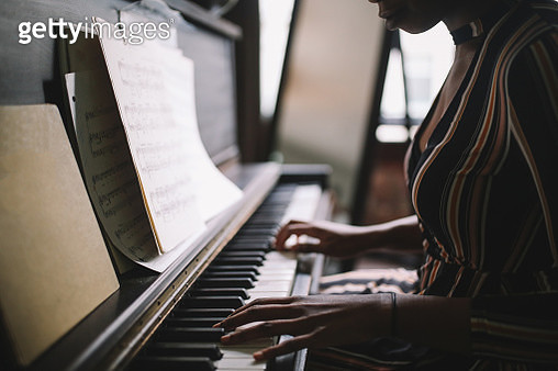 Retro toned, low key portrait of a young mixed race Latina woman practicing piano in her room in Downtown Los Angeles. - gettyimageskorea