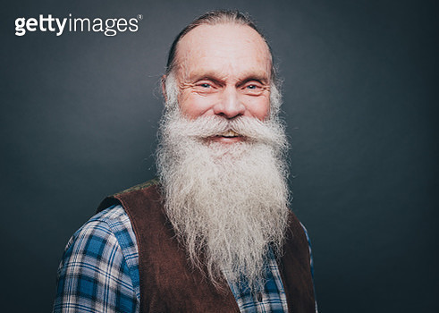 Portrait of smiling senior man with white beard and mustache against gray background - gettyimageskorea