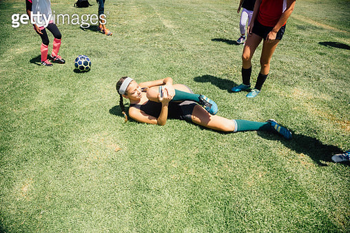 Schoolgirl soccer player lying injured on school sports field - gettyimageskorea