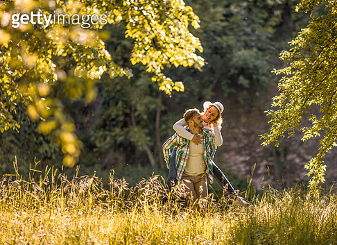 Young playful couple having fun while piggybacking in springtime outdoors. - gettyimageskorea