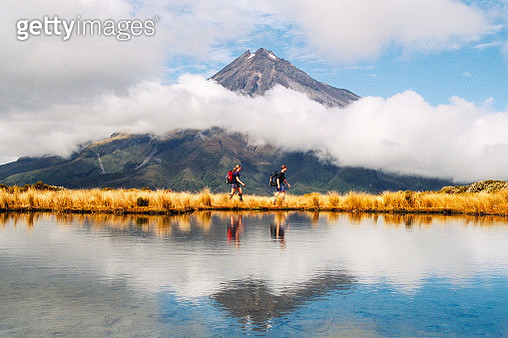 Hikers Reflection of Mount Taranaki Egmont in natural lake middle - gettyimageskorea
