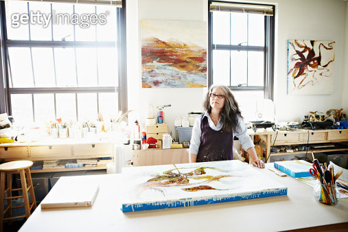 Portrait of female encaustic painter standing in studio completed painting on table in foreground - gettyimageskorea