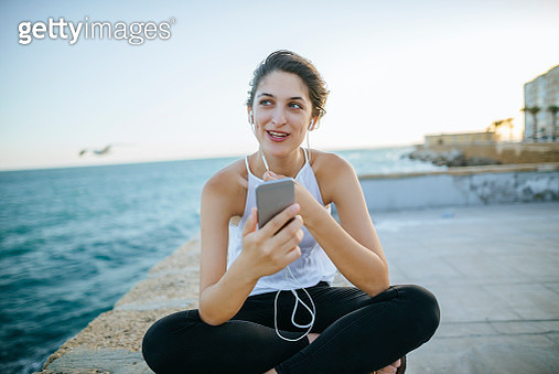 Young woman talking with hands-free phone on boardwalk - gettyimageskorea