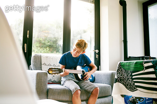 teenager playing the guitar alone on the sofa in the morning sunshine - gettyimageskorea
