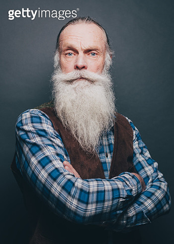 Portrait of confident bearded senior man standing arms crossed over gray background - gettyimageskorea