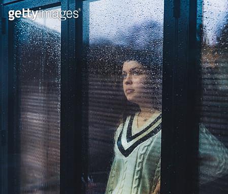 Teenage girl looking through wet window - gettyimageskorea