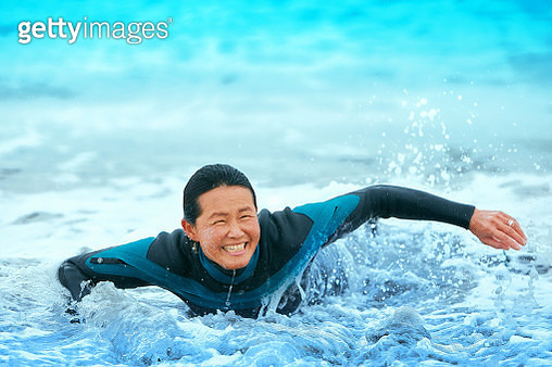 Surfer paddling with surfboard on Japanese beach in splash. - gettyimageskorea