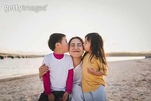 Kids kissing mother  in the beach at dusk - gettyimageskorea