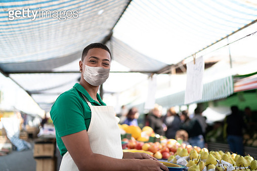 Portrait of a young woman working in a street market - with face mask - gettyimageskorea