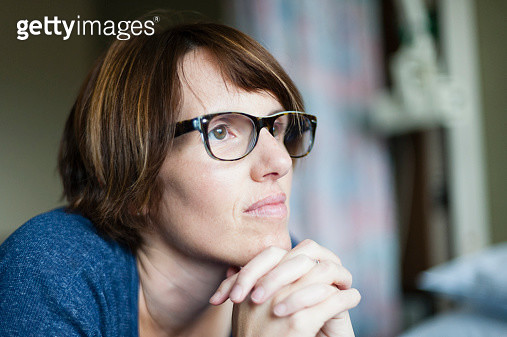 Caucasian woman thinking with hands clasped - gettyimageskorea