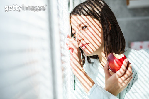 Portrait of a young brunette in bathrobe enjoying sunny morning by the window. She is eating an apple. - gettyimageskorea