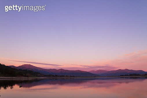 Beautiful Patagonia landscape of Andes mountain range with high mountains with illuminated peaks, stones in mountain lake, reflection, violet sky and fog at the sunset. - gettyimageskorea