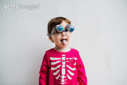 Halloween Baby girl wearing skeleton costume amb with fake horror eye glasses and tongue out - gettyimageskorea