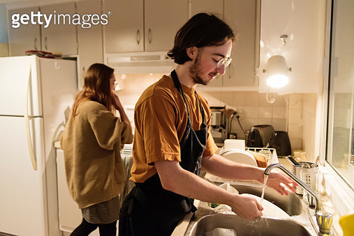Real millennial couple of students sharing life and resources in daily life. Washing dishes routine. Both are wearing clothes in warm tones. Horizontal waist up indoors shot with copy space. - gettyimageskorea