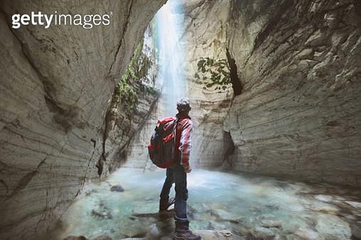Senior man looking at waterfall inside of marble cave - gettyimageskorea