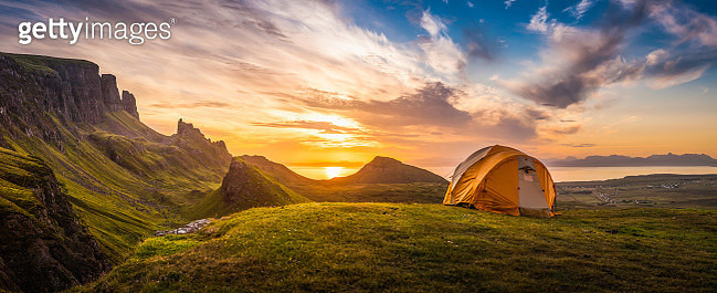Dome tent illuminated by the warm glow of sunrise as a golden cloudscape reveals the dramatic mountain pinnacles of this panoramic landscape. ProPhoto RGB profile for maximum color fidelity and gamut. - gettyimageskorea