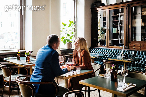Couple Drinking Red Wine At Restaurant Table Together - gettyimageskorea