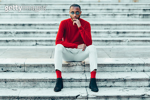 Portrait of stylish young man wearing red pullover and socks sitting on stairs - gettyimageskorea