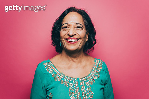 Portrait of smiling senior woman wearing salwar kameez against pink background - gettyimageskorea