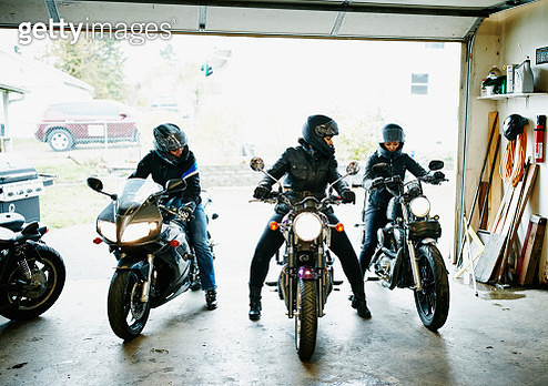 Three women on motorcycles backing out of garage - gettyimageskorea