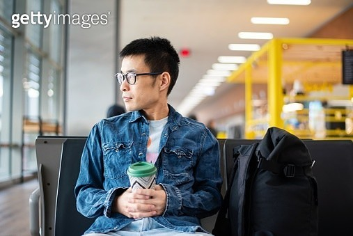 A mid adult man waiting at a terminal with his backpack and a reusable coffee cup. - gettyimageskorea